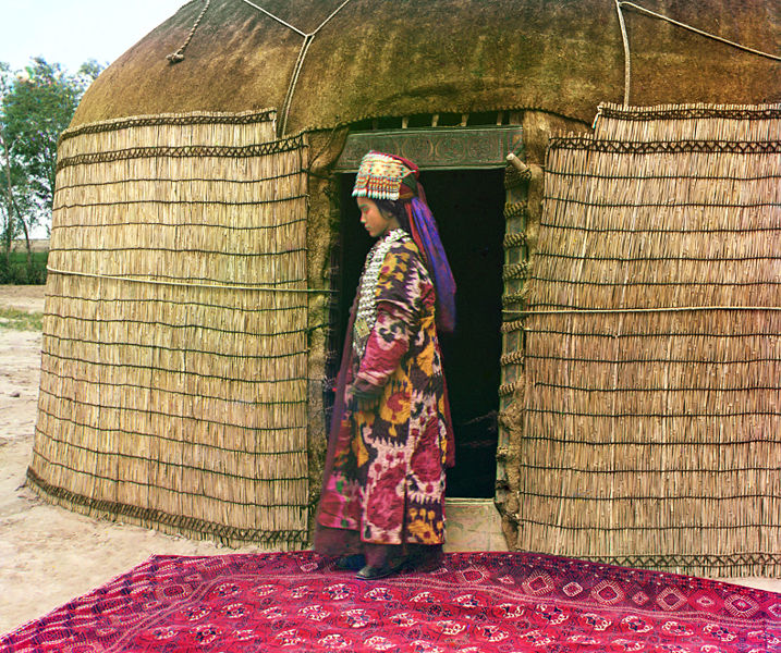 Turkman woman at the entrance to a yurt, dressed in traditional clothing and jewelry